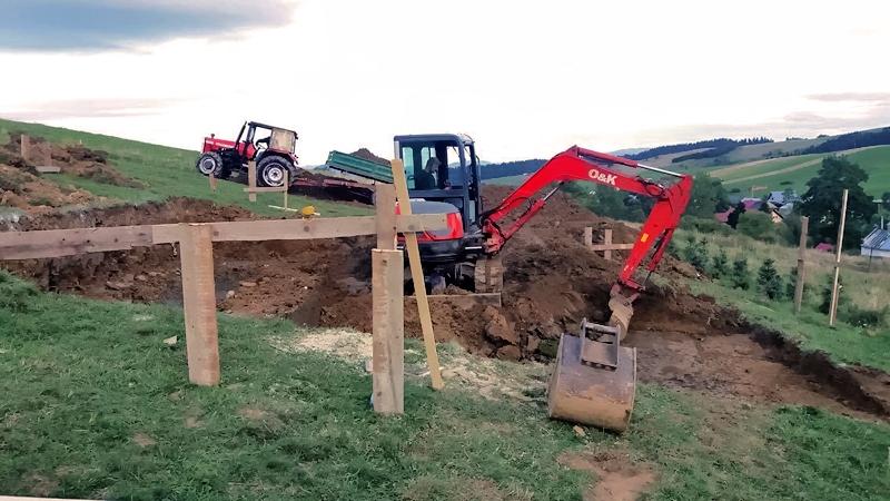 wykonanie wykopu na fundament, ciągnik w oddali stoi wzdłuż spadku stoku i widać przewyższenie
